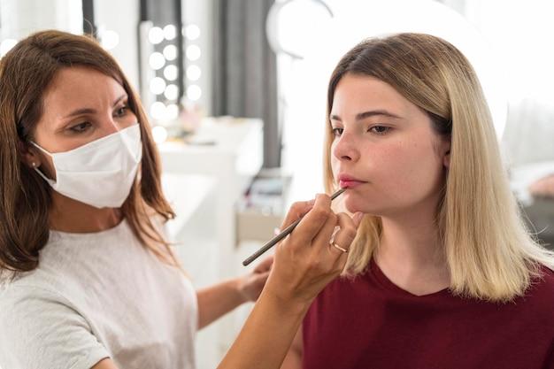 Artista de maquillaje con máscara médica y cliente