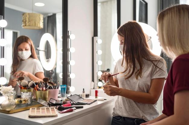 Artista de maquillaje con máscara médica