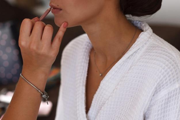 Artista de maquillaje pinta chica de lápiz labial.