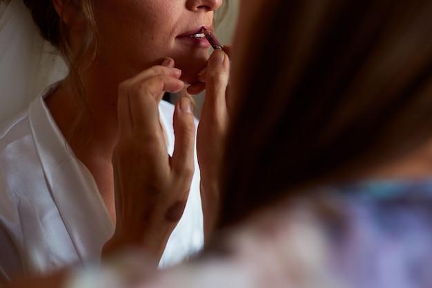 Artista de maquillaje pinta los labios de la novia con un lápiz labial rojo