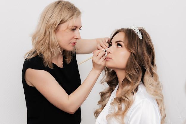 Artista de maquillaje pinta los ojos de una novia chica en un salón de belleza