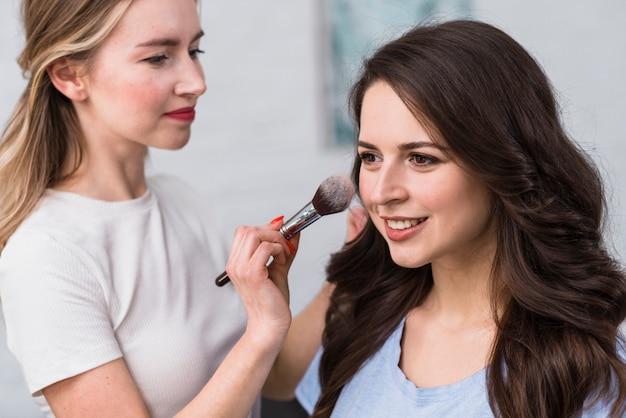 Artista de maquillaje en polvo para la cara del modelo.