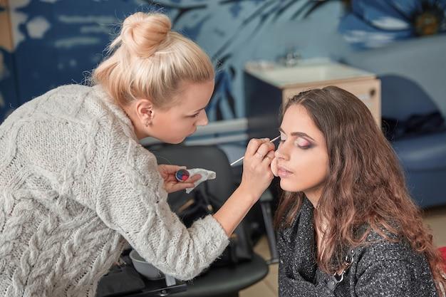 Artista de maquillaje pone sombras en los párpados de una mujer joven