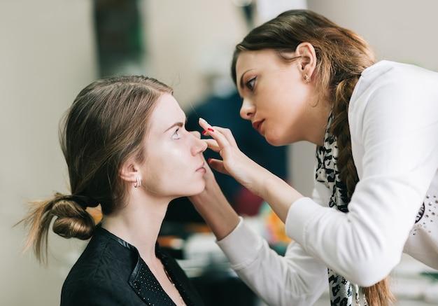 Artista de maquillaje preparando a la novia antes de la boda en una mañana