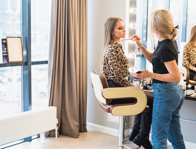 Artista de maquillaje que aplica el polvo en cara de la mujer con el cepillo