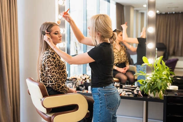 Artista de maquillaje que aplica el polvo en cara de la mujer
