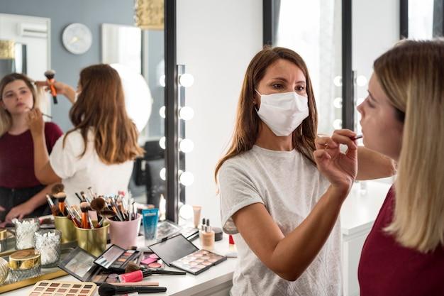 Artista de maquillaje con reflejo de máscara médica en el espejo