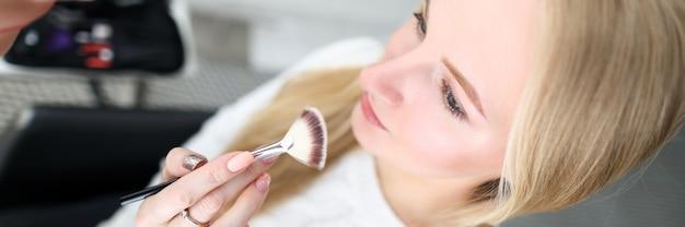 Artista de maquillaje sostiene cepillo cosmético cerca de modelo de cara