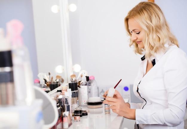 Artista de maquillaje en su lugar de trabajo en el espejo preparando herramientas para comenzar