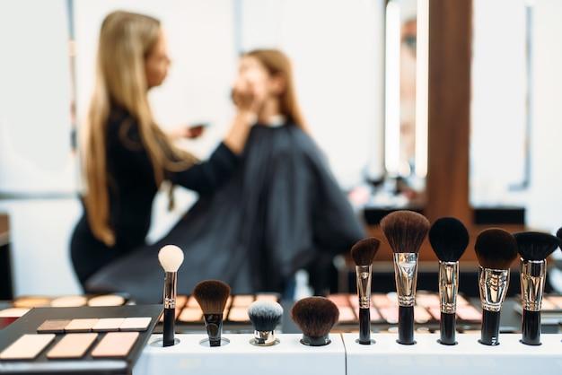 Artista de maquillaje trabaja con la cara de los clientes