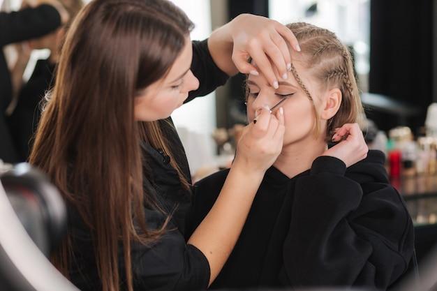 Artista de maquillaje trabaja con hermosa modelo de cabello rubio en estudio hasta que la cámara filma el proceso de maquillaje