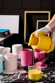 Artista mezclando pintura de latas