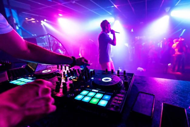Artista con micrófono realiza en el escenario de una discoteca