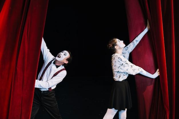 Artista de mimo masculino y femenino empujando la apertura de la cortina roja