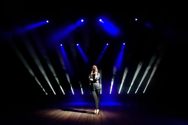 Artista de mujer bonita sobre el fondo de focos borrosos en el escenario