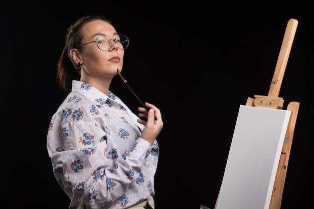 Artista mujer con pincel y pinturas en sus manos se encuentra cerca del caballete y mira a la cámara. foto de alta calidad
