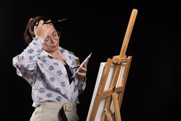 Artista mujer sosteniendo pincel y mirando lienzo sobre fondo negro