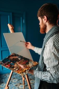 artista con paleta y pincel delante de caballete