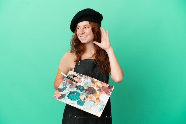Artista pelirroja adolescente sosteniendo una paleta aislada sobre fondo verde escuchando algo poniendo la mano en la oreja