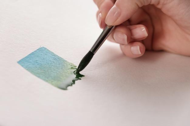 Artista pintando rayas de colores con pincel sobre papel blanco