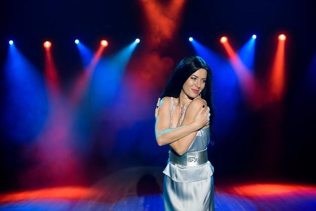 Artista posando en la escena del club. iluminación de escenario brillante