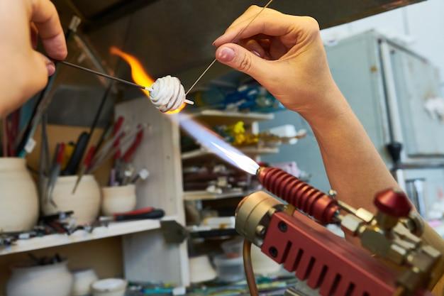 Artista que forma perlas de vidrio en llamas