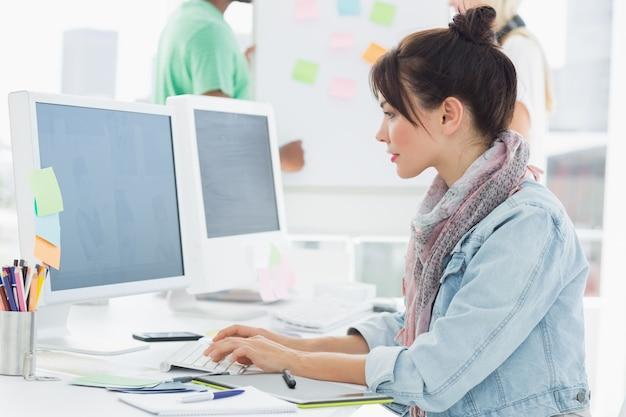 Artista que usa la computadora con los colegas detrás en la oficina