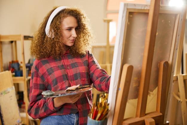 Artista rizado escucha música a través de auriculares y dibuja una pintura