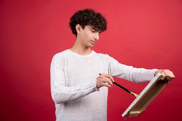 Artista rizado pintando algo sobre lienzo.