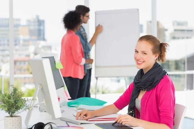 Artista de sexo femenino que usa la tableta gráfica con los colegas en la oficina