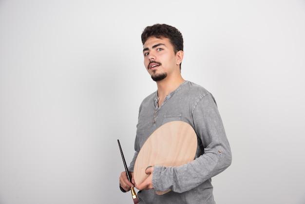 Artista sosteniendo su tablero de paleta de madera y pincel.
