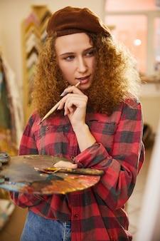 La artista sostiene un pincel y está pensando durante su trabajo.