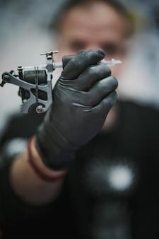 Artista del tatuaje sosteniendo y mirando una máquina de tatuaje
