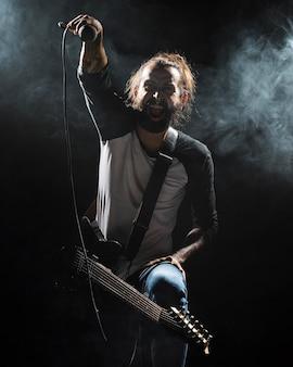 Artista tocando guitarra y efecto humo.