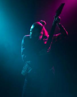 Artista tocando la guitarra en hermosas luces del escenario