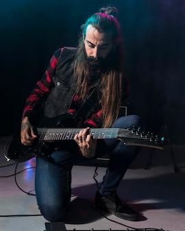 Artista tocando la guitarra y sentado en su rodilla