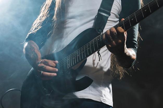 Artista tocando guitarra tiro medio