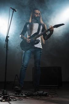 Artista tocando la guitarra vista larga