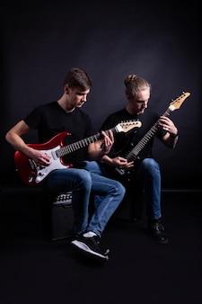 Artistas de la banda de rock tocando guitarras.
