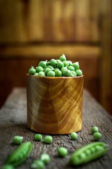 Arvejas frescas verdes sobre un fondo de madera