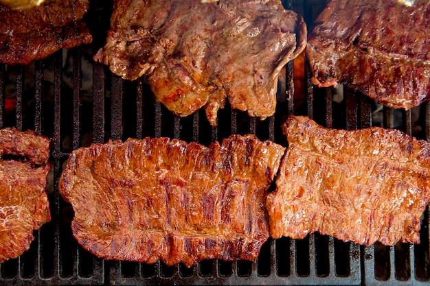 Asado de carnes a la barbacoa a la parrilla con brasas y humo.