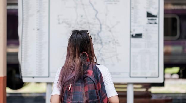 Asain mujer mira el mapa para buscar un lugar para viajar en vacaciones, ella está en la estación de tren eléctrico