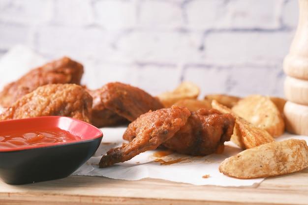 Asar gajos de pollo y camote en una tabla