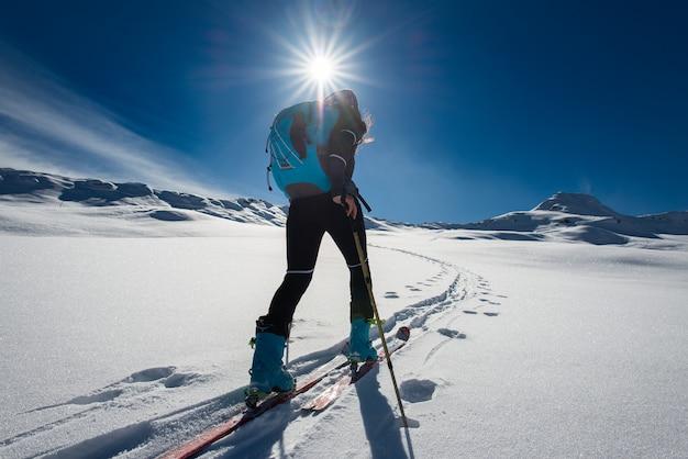 Ascenso con esquí de montaña y pieles de escalada para una mujer soltera