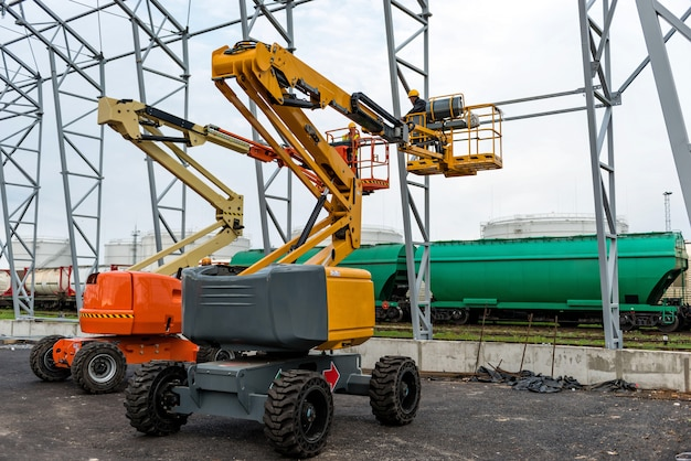Ascensor con plataforma de trabajo en campo de construcción de hangar de almacén.