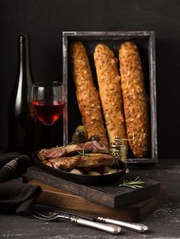 Ase el filete de cerdo en una vieja tabla de cortar de madera rústica en una cocina campestre con vino tinto y baguette francés en la pared de madera negra