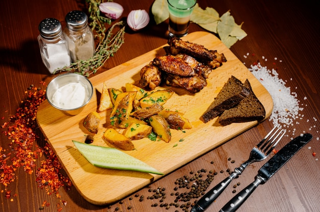 Ase a la parrilla las alas de pollo asadas de cerca con las patatas fritas, salsa en fondo de madera. concepto de comida de carne vista superior