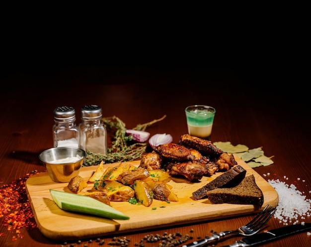 Ase a la parrilla las alas de pollo asadas de cerca con las patatas fritas, salsa en fondo de madera. concepto de comida de carne.