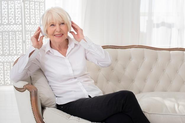 Aseado anciana sentada en el sofá con auriculares