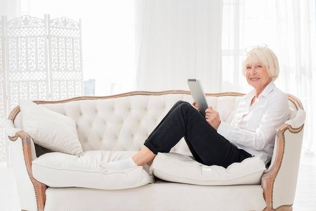 Aseado anciana sentada en el sofá con una tableta
